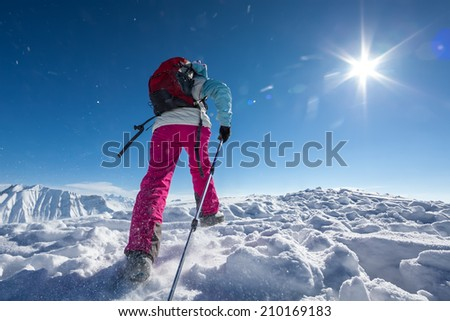 Hiker posing at top of snowy mountain during sunny day - stock photo