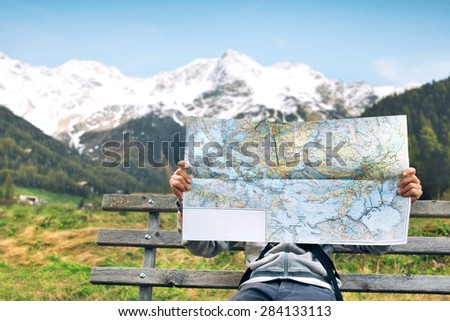 Hiker reading a geographic map choosing best trails - stock photo
