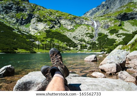Hiker resting over the glacier lake with a waterfall in the background in high mountains. Taken in High Tatras, Slovakia, Europe.  - stock photo