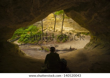 Hiker rests in natural cave - stock photo