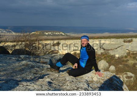 Hiker's portrait in evening mountains - stock photo