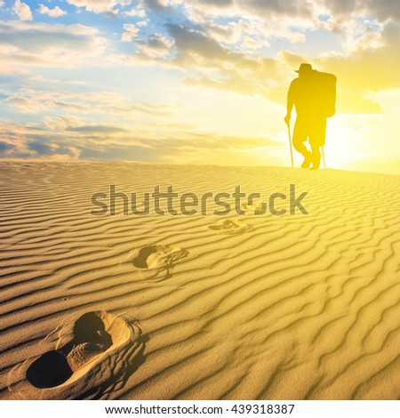 hiker silhouette at the sunset in a desert - stock photo