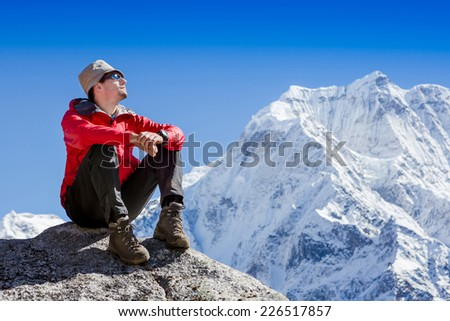 Hiker sitting on top of a mountain and enjoying Himalayas view  - stock photo