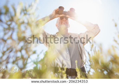 Hiker standing on country trail looking through binoculars on a sunny day - stock photo