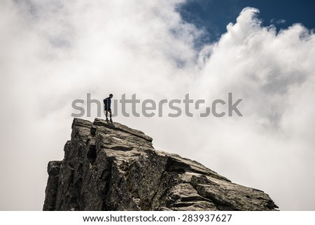 Hiker standing on steep rocky mountain summit without protection. Dramatic cloudy sky. Concept of reaching the goal and conquering the success. Contrasted, silhouette like. - stock photo