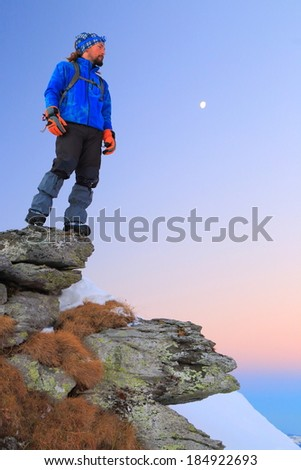 Hiker standing on the mountain edge under full moon - stock photo