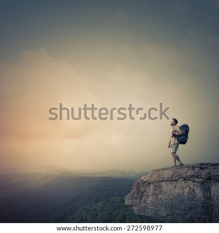 Hiker standing on top of the mountain with backpack - stock photo