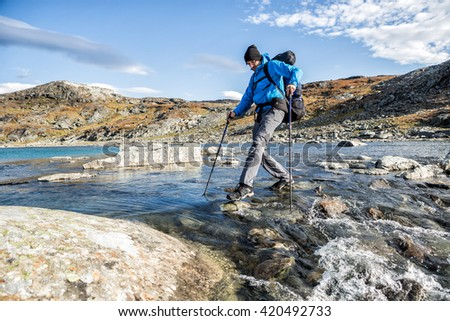 Hiker takes a River in northern Sweden - stock photo