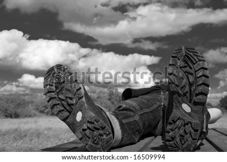 hiker taking a rest on a summer-day.Focus on bottom of hiking-boots - stock photo