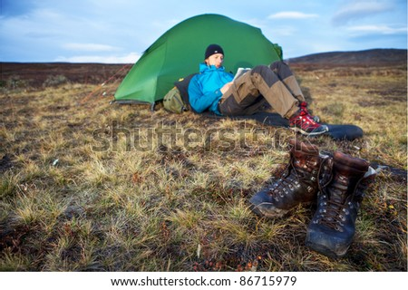 Hiker, Tent and Hiking Boots in Sweden in Autumn - stock photo