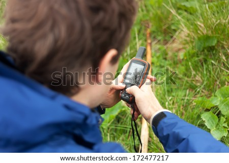 Hiker tracks his position at the gps - stock photo