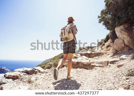 Hiker traveler woman on a hiking trail, travel and active lifestyle concept - stock photo