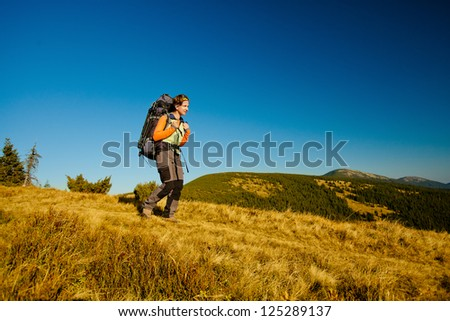 Hiker walking in autumn mountains. Caucasian model outdoors in nature - stock photo