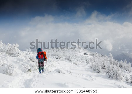 Hiker walking in snowy mountains  - stock photo