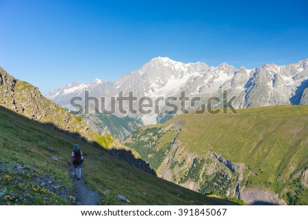 Hiker walking uphill on footpath with great panoramic view over the Mont Blanc massif and mountain peak (4810 m). Backpacker's summer adventures and wanderlust in Valle d'Aosta, Italian French Alps. - stock photo