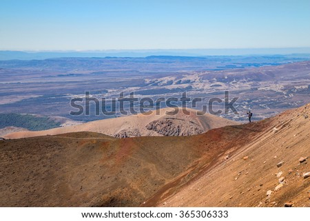 Hiker Walks on the Ridge of Red Crater in Tongariro National Park, New Zealand - stock photo