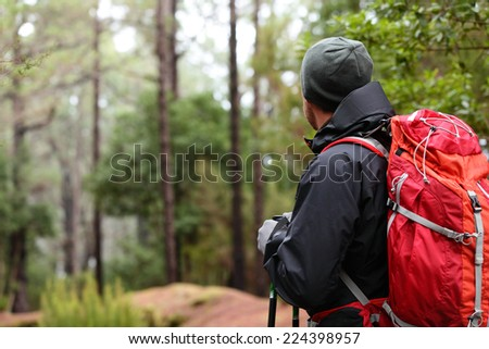 Hiker wearing hiking backpack and hardshell jacket on hike in forest. Man wearing hat gloves using hiking sticks poles outdoors in woods. Male hiker standing looking away. - stock photo