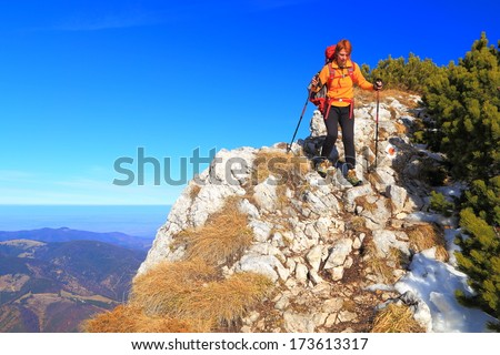 Hiker wearing yellow shirt descends the mountain in autumn day - stock photo