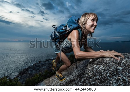 Hiker with backpack climbing natural rocky wall on a dark cloudy background. There are water drops on the skin - stock photo