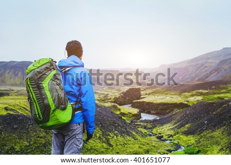 hiker with backpack enjoying beautiful panoramic view of mountains in Iceland, volcanic landscape, travel background - stock photo