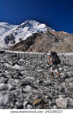 Hiker with backpack on glacier below highest peaks in Tien-Shan mountain range in Kyrgyzstan - stock photo