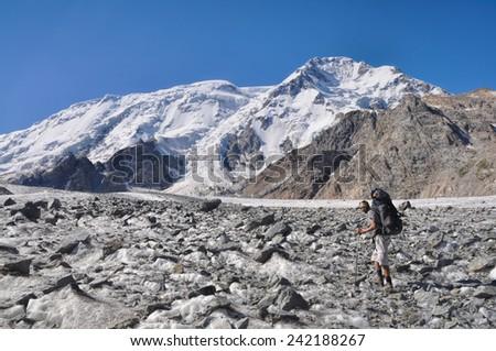 Hiker with backpack on glacier below snow-covered highest peaks in Tien-Shan mountain range in Kyrgyzstan - stock photo