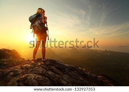 Hiker with backpack relaxing on top of a mountain and enjoying sunrise - stock photo