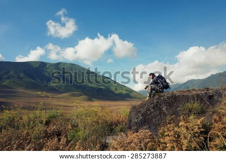 Hiker with backpack sit on stone on the mountain - stock photo
