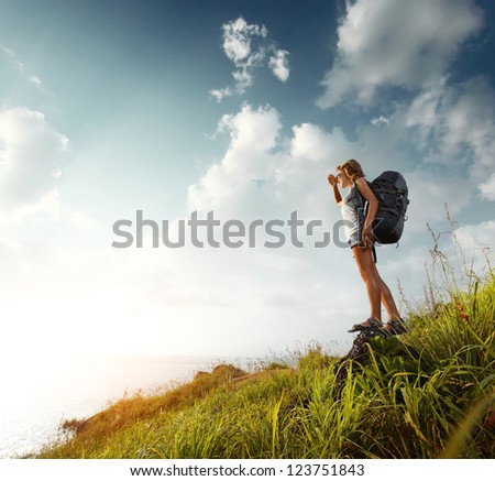 Hiker with backpack standing on a rock and looking to somewhere - stock photo