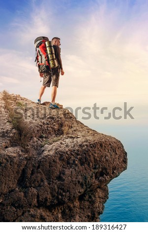 Hiker with backpack standing on top of a mountain.  - stock photo