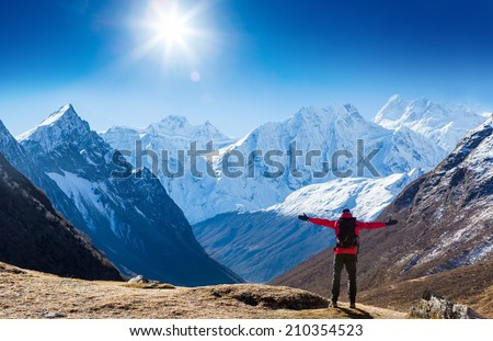 Hiker with backpack standing on top of a mountain and enjoying sun - stock photo