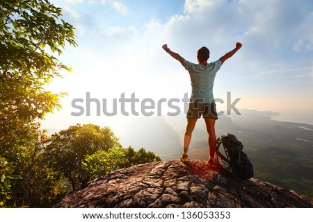 Hiker with backpack standing on top of a mountain with raised hands - stock photo