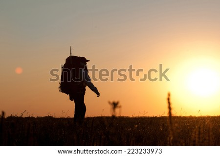 Hiker with backpack walking in the field. Over sunset. Summer healthy active lifestyle. Single travel. - stock photo