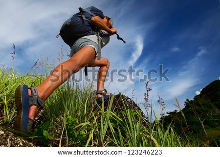 Hiker with backpack walking on a rocky terrain with green lush grass - stock photo