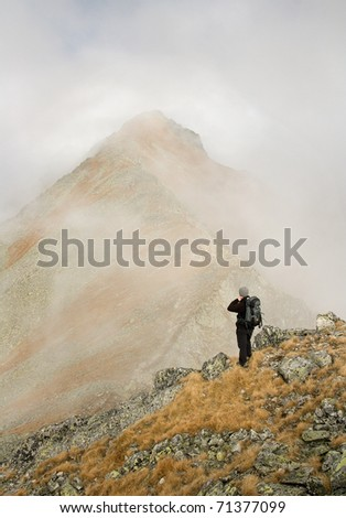 Hiker with backpacks is looking at teh cloudy mountains. Atumn Slovakian High Tatra Mountains. - stock photo