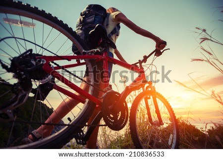 Hiker with bicycle watching sunset - stock photo