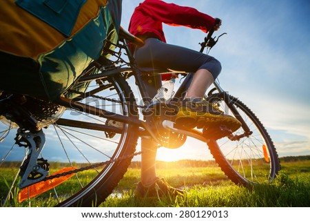 Hiker with loaded bicycle on a green summer meadow at sunset - stock photo