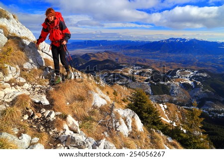 Hiker woman across grassy mountain slope in autumn - stock photo