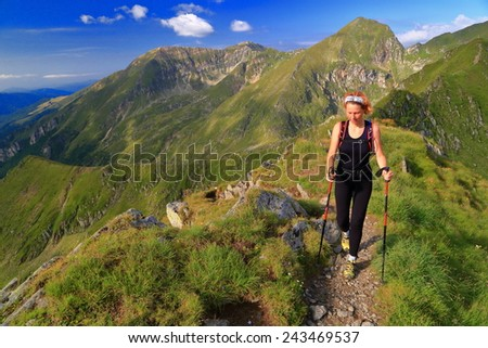 Hiker woman approaching on a mountain trail in sunny summer day - stock photo