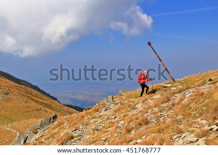 Hiker woman ascending a sunny trail in Fagaras mountains, Romania - stock photo