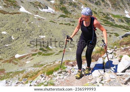 Hiker woman climb a narrow trail on the mountain side - stock photo