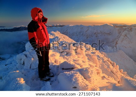 Hiker woman on top of snowy mountain illuminated by the sunset - stock photo
