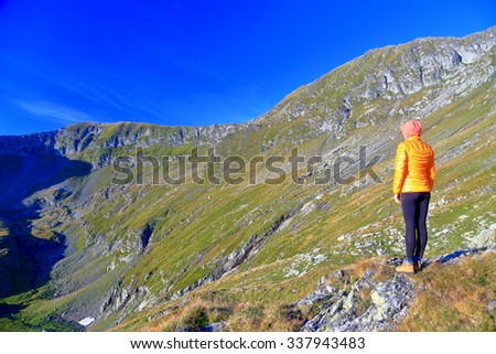 Hiker woman standing above the valley on a sunny mountain side - stock photo
