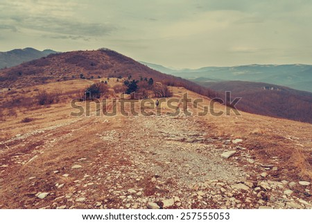 Hiker woman walking in the mountains. Concept of small person among powerful nature - stock photo
