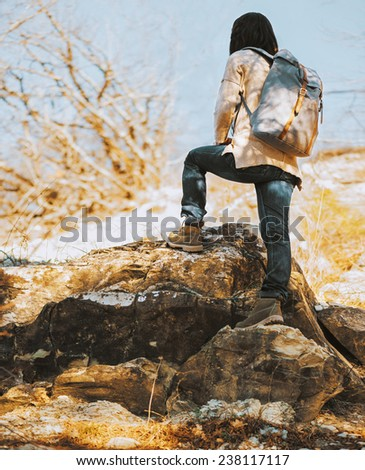 Hiker woman with backpack go up on rock, rear view. Hiking and recreation theme - stock photo