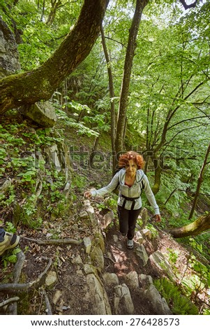Hiker woman with backpack on a forest trail in the mountains - stock photo