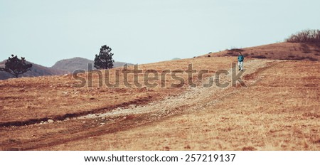Hiker young man walking down on footpath on hill in spring - stock photo
