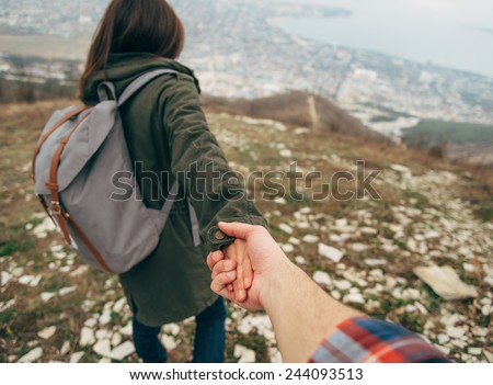 Hiker young woman holding man's hand and leading him on nature outdoor. Couple in love. Point of view shot. Focus on hands. - stock photo