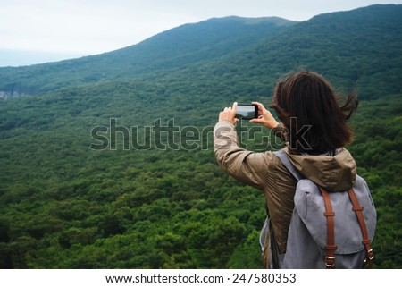 Hiker young woman with backpack taking photographs the beautiful landscape of mountain in summer - stock photo