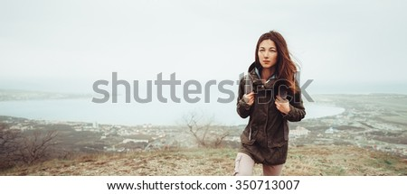 Hiker young woman with backpack walking up on mountain over the bay at cloudy weather, front view - stock photo